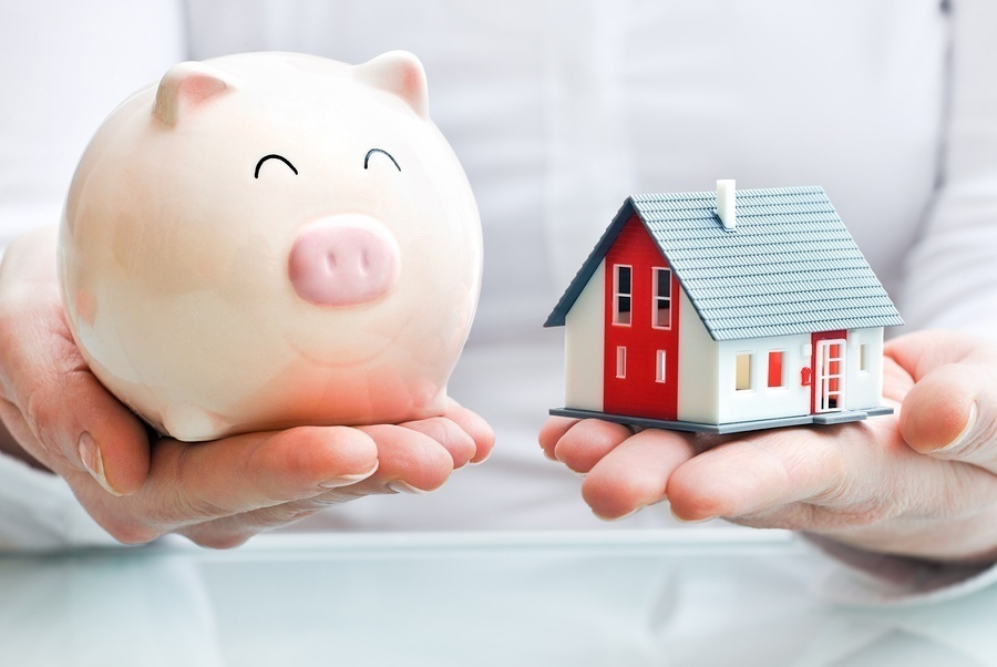 Hands holding piggy bank and house model, buying a home in bend Oregon