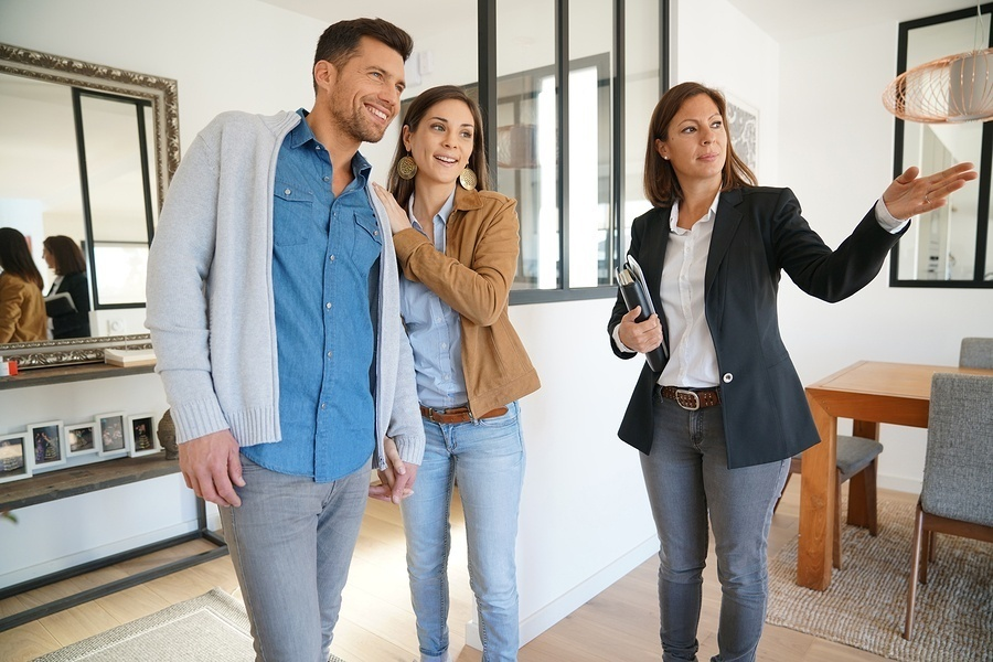 good real estate agent showing a couple a house