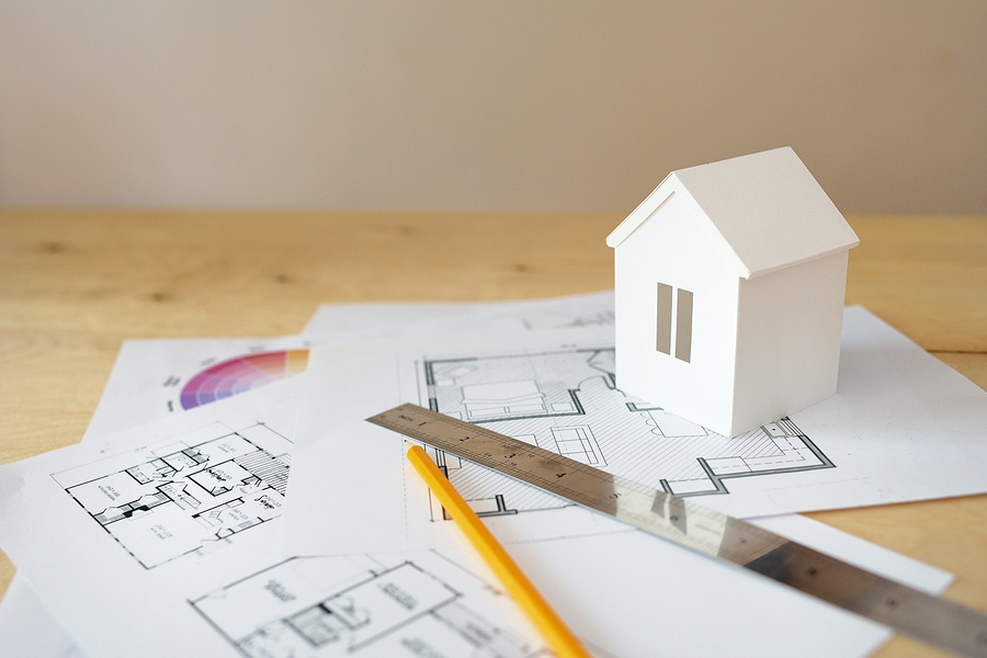 blueprints and house figurine should you remodel