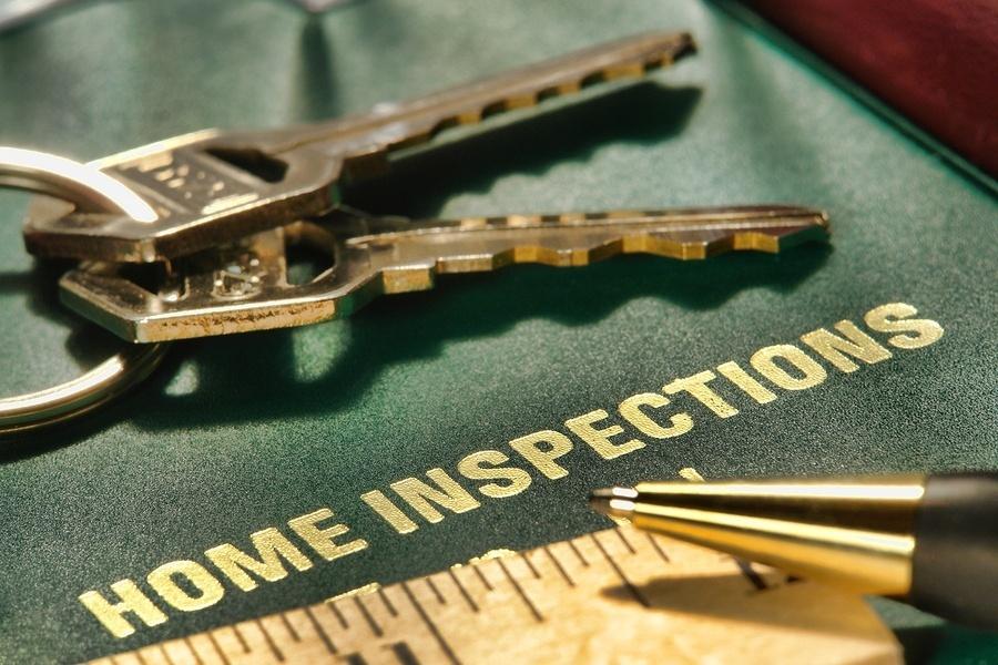 set of keys on top of real estate home inspector folder