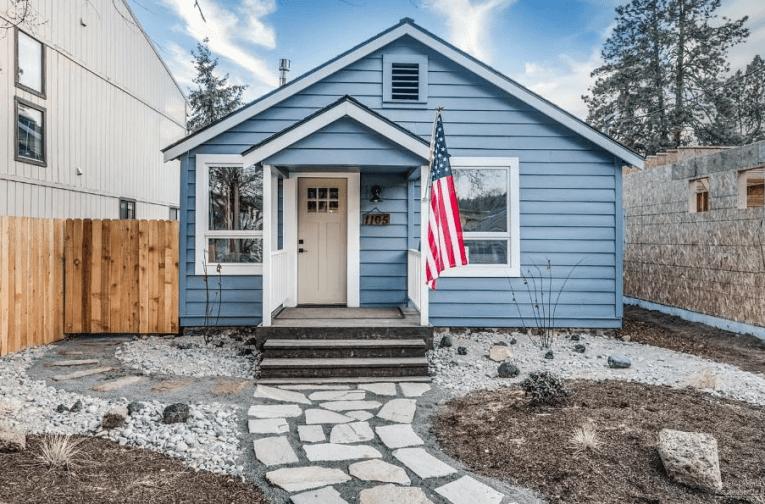 a blue house with a flag shows flip a house bend oregon